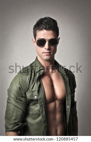 Muscular man in dark green shirt - stock photo