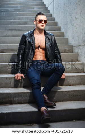 Muscular man in leather jacket and sunglasses sitting on stairs. - stock photo