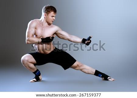 Muscular man in sportswear posing at studio. Bodybuilding. Martial arts.  - stock photo