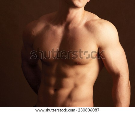 Muscular man , isolated on brown background - stock photo