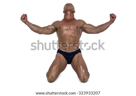 Muscular man kneeling down with arms outstretched against white background - stock photo