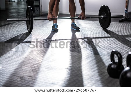 Muscular man lifting a barbell in crossfit gym - stock photo