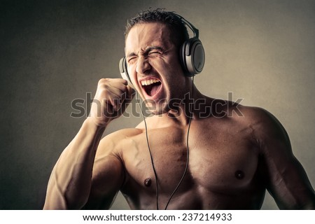 Muscular man listening to music  - stock photo