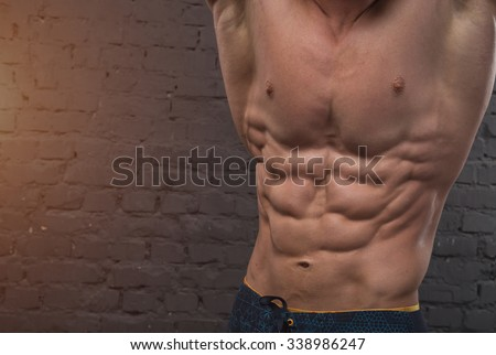 Muscular man on dark background brick wall. Close up of a handsome man's torso. Closeup of a man's body only. Very muscular body man sport. Strong man male bodybuilder. Force. - stock photo