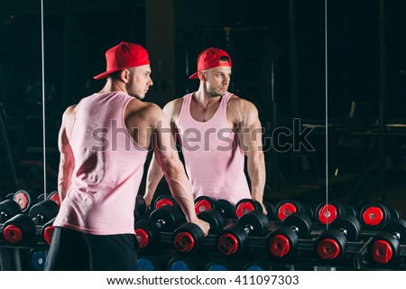 Muscular man out in gym standing near dumbbells,  a pink shirt and red baseball cap - stock photo