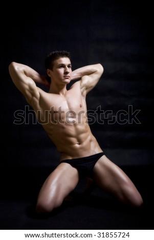 muscular man posing artistic - stock photo