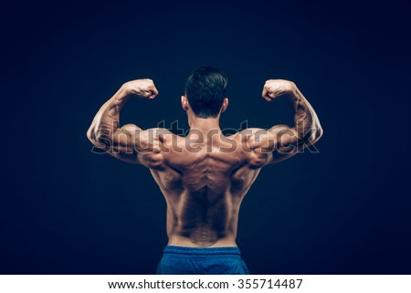 Muscular man posing in dark studio. on black background. - stock photo