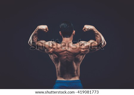 Muscular man posing in dark studio on black background. - stock photo