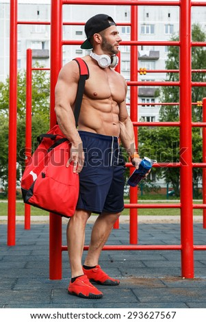 Muscular man posing on the street after his workout - stock photo