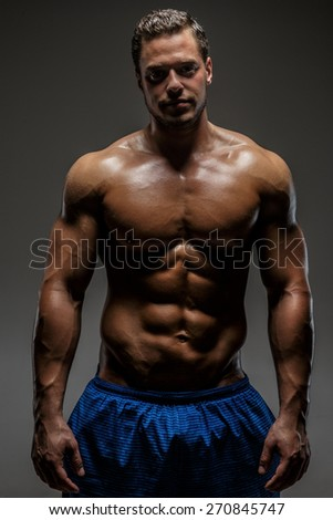 Muscular man showing his chest and stomach. Isolated on grey - stock photo