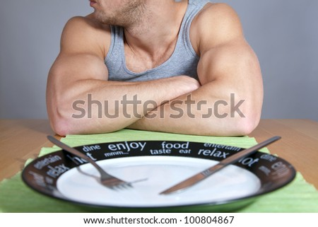 Muscular man sitting at the table with empty plate - stock photo