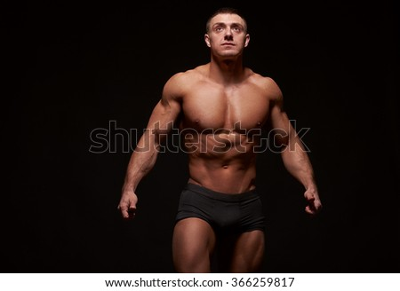 Muscular man stretching his arms out against of black background. Studio shot - stock photo