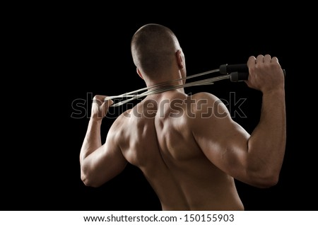 Muscular man tightening jump rope on his neck - stock photo