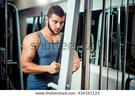 muscular man training in the fitness club. training simulator for hands . increases the volume of the arm muscles - stock photo