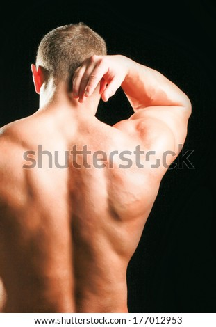 Muscular man with back neck ache isolated on black background - stock photo