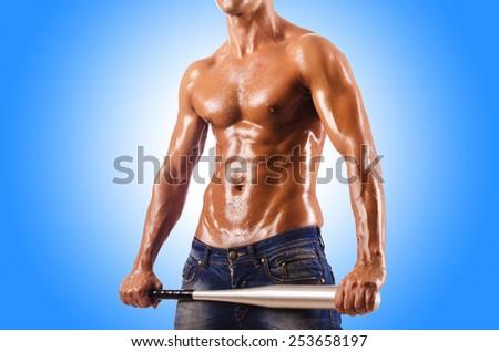 Muscular man with baseball bat - stock photo