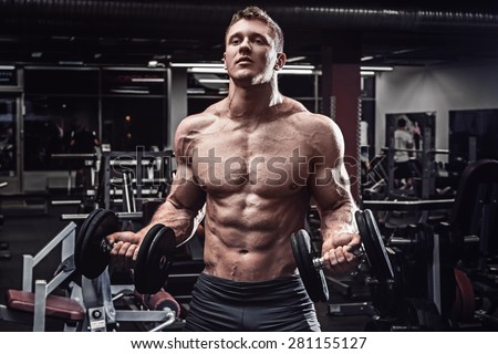 Muscular man with dumbbells in gym - stock photo