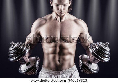 Muscular man with dumbbells on a black background - stock photo
