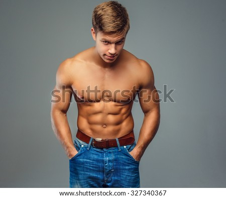 Muscular man with naked torso and hands in pockets. Isolated on grey background. - stock photo