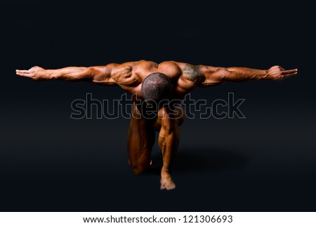Muscular man with outstretched arms to the side and his head down.isolated on a black background - stock photo