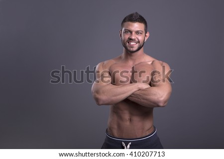 muscular man with perfect body posing without a shirt on a dark background - stock photo