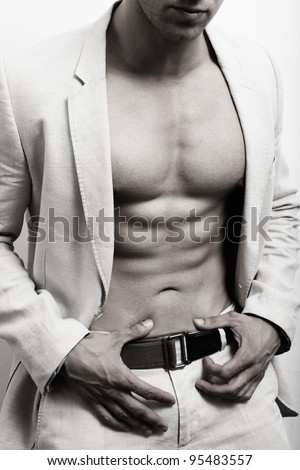 Muscular man with sexy abs and suit over white wall - stock photo