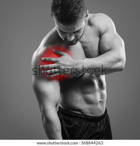 Muscular man with shoulder pain over gray background. Concept with highlighted glowing red spot. - stock photo