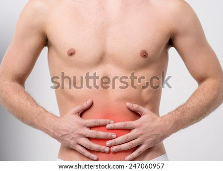 Muscular man with stomach pain - stock photo