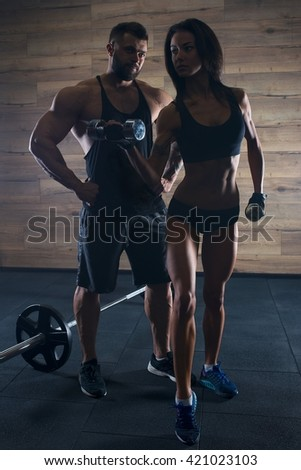 Muscular man with tattoos and beard and beauty girl posing in a black tank top and blue shorts in the gym. Silhouette - stock photo