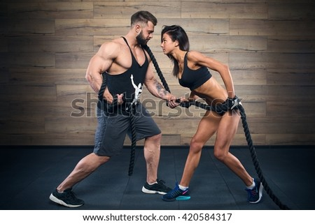 Muscular man with tattoos and beard and beauty girl pulling a rope in a black tank top and black shorts in the gym - stock photo