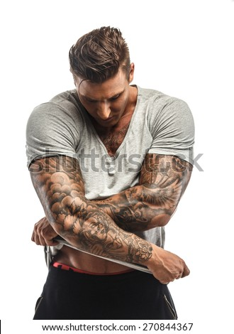 Muscular man with tattos undressing. Isolated on white - stock photo