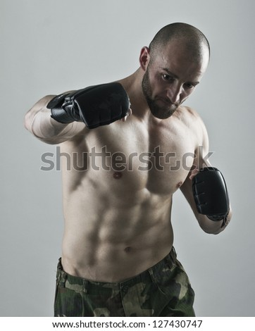 Muscular man with the gloves striking a punch. - stock photo