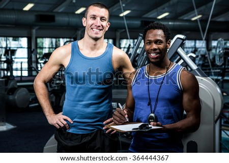 Muscular man with trainer smiling at camera at gym - stock photo