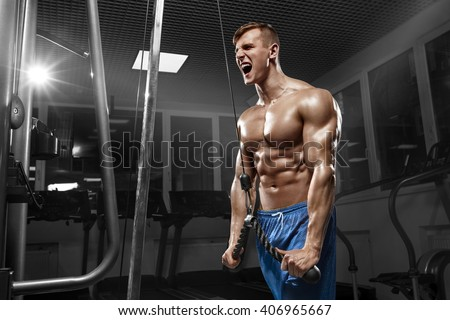 Muscular man working out in gym doing exercises at triceps, strong male naked torso abs - stock photo