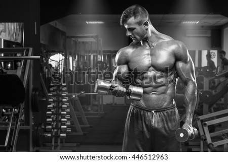 Muscular man working out in gym doing exercises with dumbbells at biceps, strong male abs - stock photo