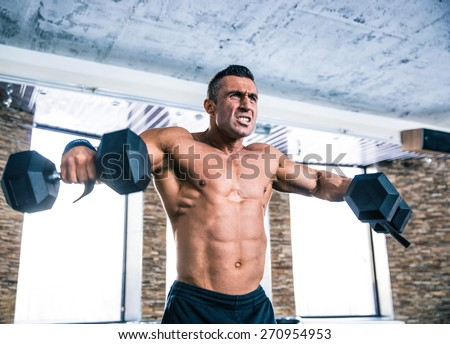 Muscular man workout with dumbbells at gym - stock photo
