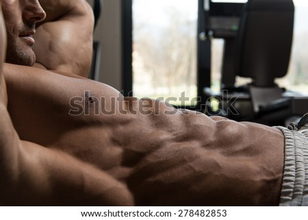 Muscular Mature Man Exercising Abdominals On Exercise Ball In Modern Fitness Center - stock photo