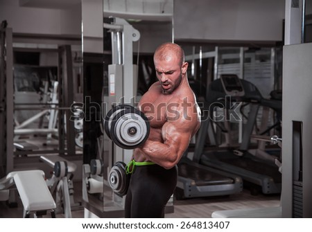 Muscular Men Exercise with dumbbells. He is performing alternate bicep curls. - stock photo