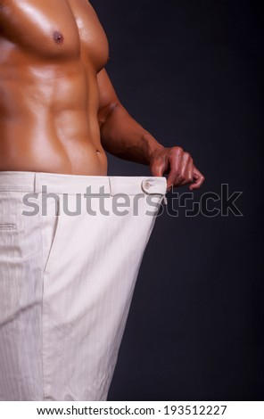 Muscular men showing how much weight he lost. Professional studio lighting - stock photo
