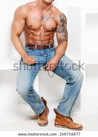 Muscular naked torso. Tattos and blue jeans - stock photo