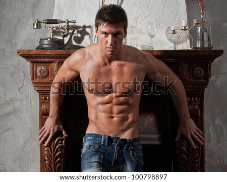 Muscular relief sexy naked man posing in the studio in jeans near the fireplace - stock photo
