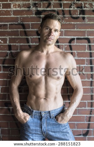 Muscular shirtless Caucasian man in blue jeans standing against brick wall with graffiti in urban setting - stock photo