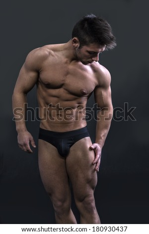 Muscular shirtless young man touching and looking at his own thighs and legs - stock photo