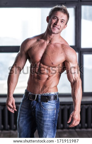 Muscular smiling young sexy guy posing in studio in jeans and bare-chested - stock photo