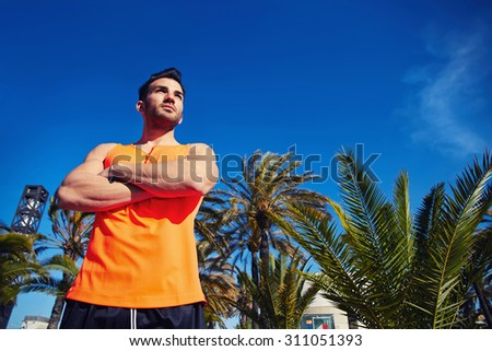 Muscular sportsman resting after an active workout outdoors standing against sky and palm trees background with copy space area for your advertising content, male runner took a break after training - stock photo