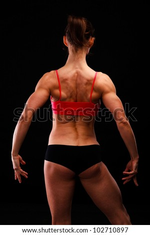 Muscular strong woman posing against a black background - stock photo