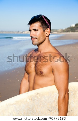 Muscular surfer holding his surf board overlooking the ocean. - stock photo