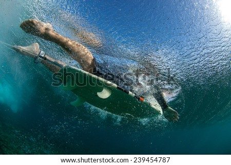 muscular surfer with long white hair riding on big waves on the Indian Ocean island of Mauritius, picture was taken under water - stock photo