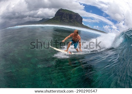 muscular surfer with long white hair riding on big waves on the Indian Ocean island of Mauritius - stock photo