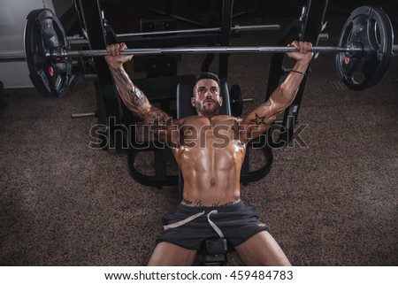 Muscular tattoo man in the gym. - stock photo